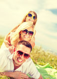 在说谎在毯子的太阳镜的微笑的家庭 免版税库存照片