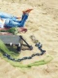 在说谎在沙子的格子花呢披肩毯子的牛仔裤、男人和妇女的腿在与valise的海滩 库存图片