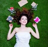 在说谎在的礼物和购物车附近的美丽的少妇 免版税库存照片