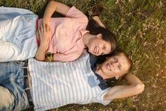 在说谎在绿草的爱的夫妇 免版税库存图片
