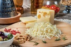 在说谎在b的一个木板的磨丝器的被磨碎的荷兰扁圆形干酪 免版税库存照片