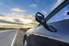 在直路和五颜六色的明亮的日落天空的跑车 库存图片