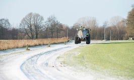 在冻路的施肥拖拉机在农村冬天环境美化 图库摄影