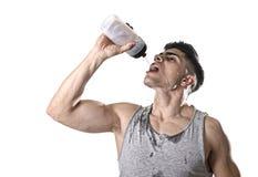 年轻在满身是汗的面孔的体育运动人渴饮用的含水瓶倾吐的流体 库存照片