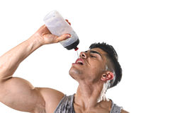 年轻在满身是汗的面孔的体育运动人渴饮用的含水瓶倾吐的流体 免版税库存照片