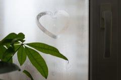 在满身是汗的玻璃窗的题字,心脏形状  爱和浪漫史标志 库存照片
