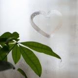 在满身是汗的玻璃窗的题字,心脏形状  爱和浪漫史标志 免版税库存图片