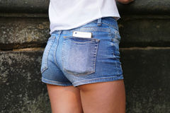 在紧身短裤或赃物短裤的后面口袋的巧妙的电话 库存照片