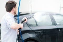 在洗车驻地的人洗涤的汽车 免版税库存图片
