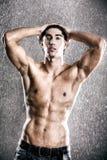在年轻人之下的人肌肉雨 库存照片