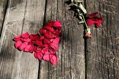 在年迈的木桌上的红色玫瑰花瓣心脏 免版税库存图片