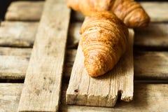在年迈的木箱子和板条,关闭的新鲜的新月形面包,金黄外壳,酥饼,土气葡萄酒样式 免版税库存图片