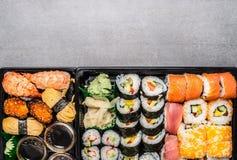 在黑运输箱子或bento箱子的各种各样的寿司菜单在灰色石背景,顶视图 图库摄影