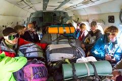 在货运直升机里面的乘客有许多背包的 免版税库存照片
