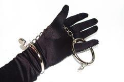 在黑迷信手套的钢手铐 免版税库存照片