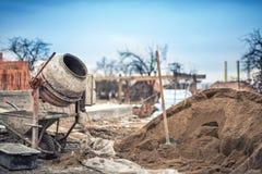 在建造场所、工具和沙子的水泥搅拌车机器 库存照片