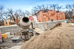 在建造场所使用的水泥搅拌车机械为准备灰浆和修筑墙壁 免版税库存照片