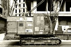 在建造场所前面的老起重机 免版税库存照片