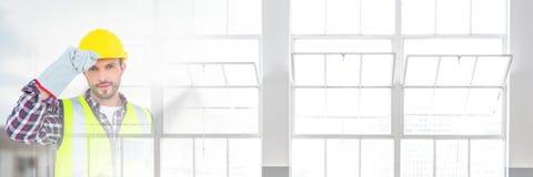 在建造场所前面的建筑工人有窗口转折作用的 免版税库存图片