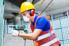 在建造场所墙壁的亚洲工作者钻井 库存图片