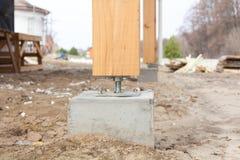 在建造场所混凝土的木柱子与螺丝 木柱子是在基础或Pla可以被安置的结构 图库摄影