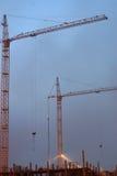 在建造场所的两台起重机,配件在一个未完成的房子里,有雾的晚上微明 图库摄影