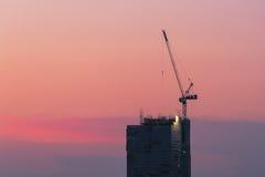 在建造场所的工业起重机有日落天空的 免版税库存照片