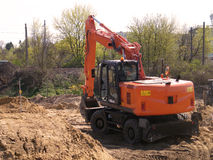 在建造场所的橙色挖掘机在沙子中小丘  免版税图库摄影