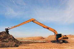 在建造场所的橙色挖掘机 图库摄影