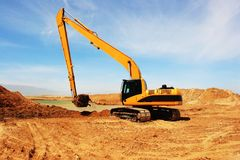 在建造场所的橙色挖掘机 免版税图库摄影