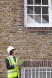 在建造场所的年轻男性监督员文字笔记 图库摄影