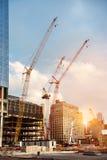 在建造场所的建筑用起重机在纽约修建办公室摩天大楼大厦在日落时间 免版税库存照片