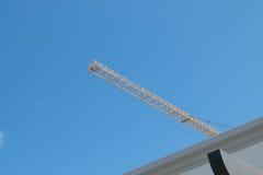 在建造场所的黄色高长的起重机箭头与光亮的浅兰的天空天 免版税库存照片