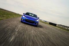 在滚道的蓝色跑车 库存图片