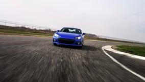 在滚道的蓝色跑车 免版税图库摄影