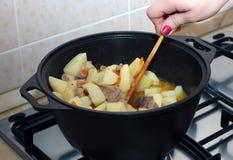 在黑金属罐的妇女的手stiring的蔬菜炖肉 免版税库存照片
