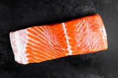 在黑金属背景,顶视图的未加工的三文鱼或鳟鱼海鱼内圆角 图库摄影