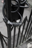 在黑铁篱芭的自行车锁 免版税库存图片