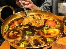 在黄铜热的罐的传统地道泰国草本汤食物:在热的罐的热和酸猪肉汤,汤姆猪肉汤,也是Tomyam Moo 库存照片
