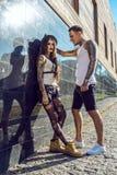 在黑铺磁砖的墙壁的年轻时髦的被刺字的夫妇在街道上 免版税库存照片