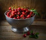 在滤锅的红色樱桃在黑暗的木背景 库存照片