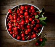 在滤锅的水多的红色樱桃在木背景 免版税图库摄影