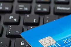 在黑键盘的蓝色信用卡 免版税库存照片