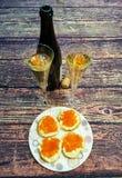 在从长方形宝石的木桌三明治用在板材和杯的红色鱼子酱香槟和一个瓶香槟 免版税库存照片