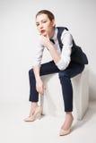 在黑长裤、上面、蝶形领结和背心的时装模特儿坐在白色的立方体 免版税图库摄影