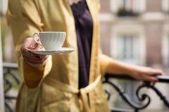 在巴黎阳台的妇女提供的咖啡 库存图片