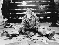 在他附近供以人员坐在与残破的板材的一个楼梯前面(所有人被描述不更长生存,并且庄园不存在 库存图片