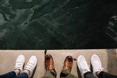 在水附近的三个人 腿和水 在水附近的鞋子 库存图片