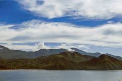 在水附近的美丽的山在美丽的天空下 免版税库存照片