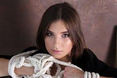 在绳索附近被包裹的年轻美丽的女孩的手 画象 工作室 库存图片